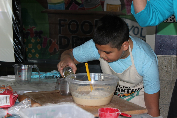 Hilltop students make dough to bake bread for themselves and to donate to a local food shelter.