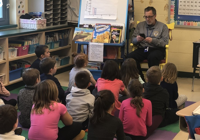 Officer Behre reads to students